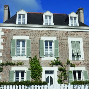 Saint-Malo, France - July 7, 2011: Villa built with traditional granite stones and french doors in Rotheneuf, a suburb of Saini-Malo. Rotheneuf is a seaside resort and famous for its sculpted rocks.
